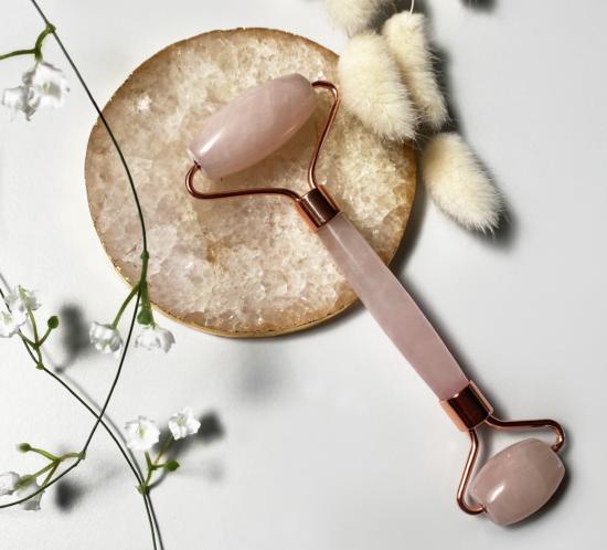 Rosenquarz Gesichtsmassage Roller Roségold Flat Lay auf schönem Hintergrund