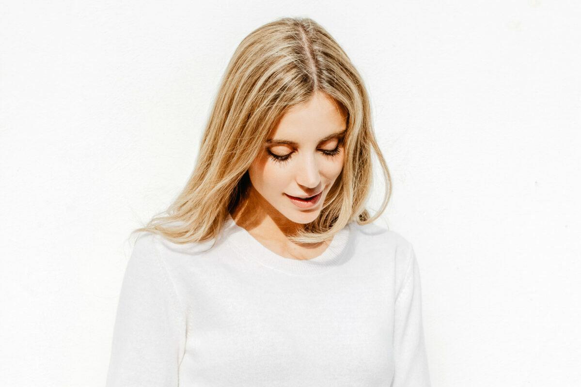 Eine junge, blonde Frau vor weissem Hintergrund, die verträumt zu Boden blickt, trägt offenes Haar, stylt sich mit Produkten von Trisa Accessoires