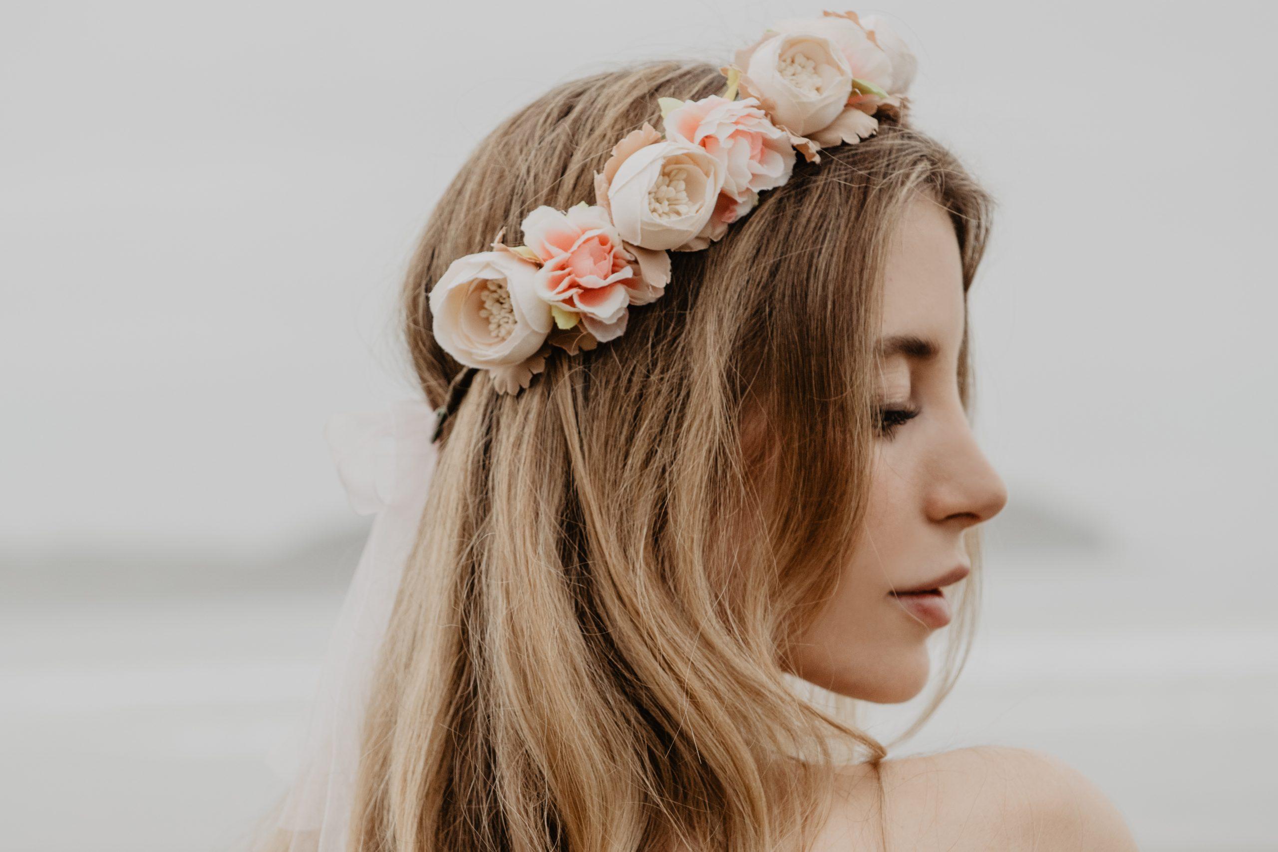 Verträumte junge Frau mit blonden Haaren trägt einen romantischen Blumenkranz im Haar von CELEBRIDE Trisa Accessoires, am Strand in Ibiza