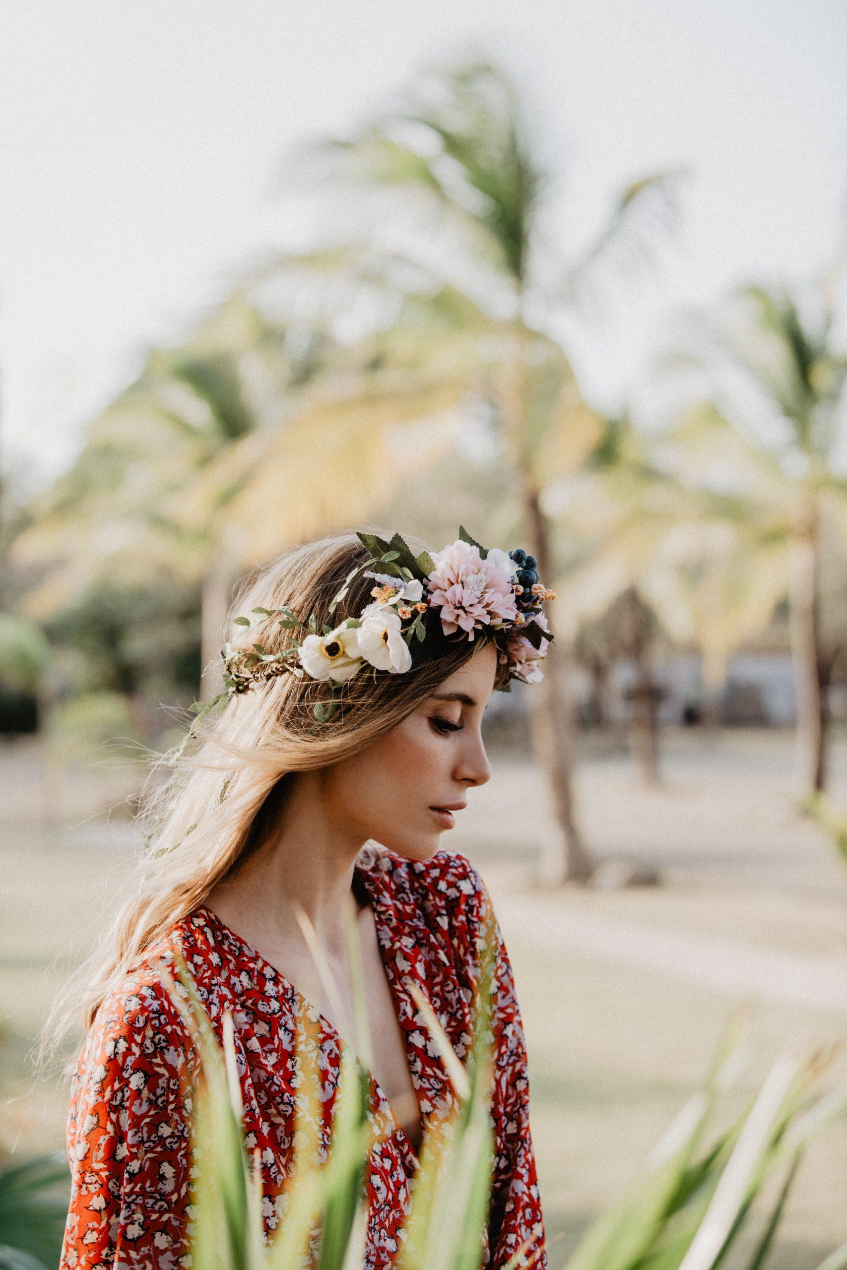 Eine junge Frau mit Blumenkranz von CELEBRIDE Trisa Accessoires, spaziert am Sand Strand von Panama, mit Palmen im Hintergrund.