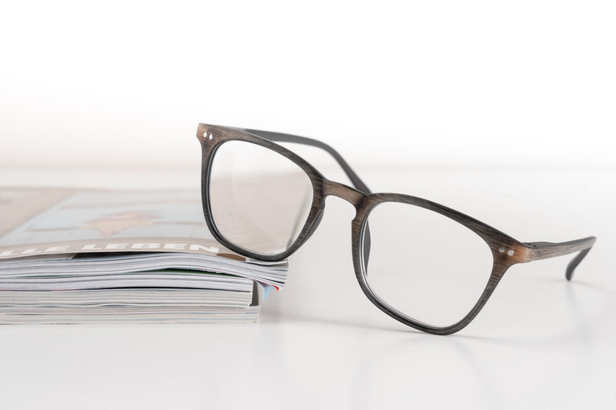Modische Lesebrille in Holzoptik von nVisio Trisa Accessoires, liegt auf Magazinen, auf weissem Hintergrund.