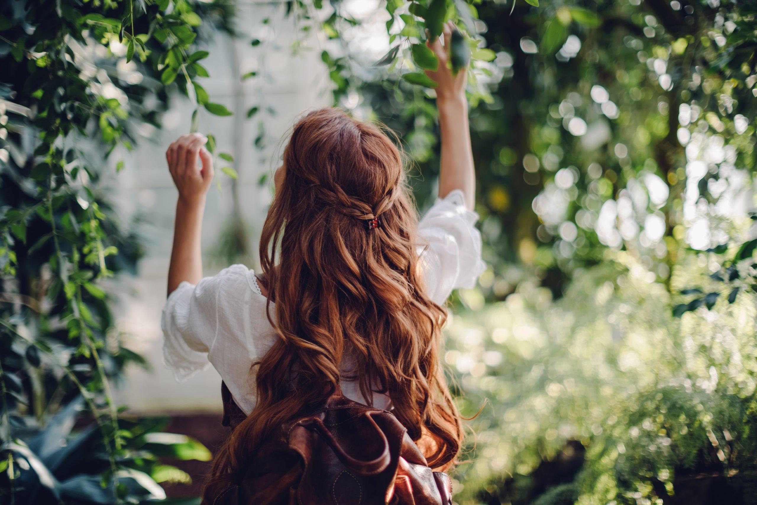 Eine junge Frau in der Natur, mit brünetten langen Locken, trägt Rucksack von Trisa Accessoires und Nachhaltigkeit ist ihr wichtig