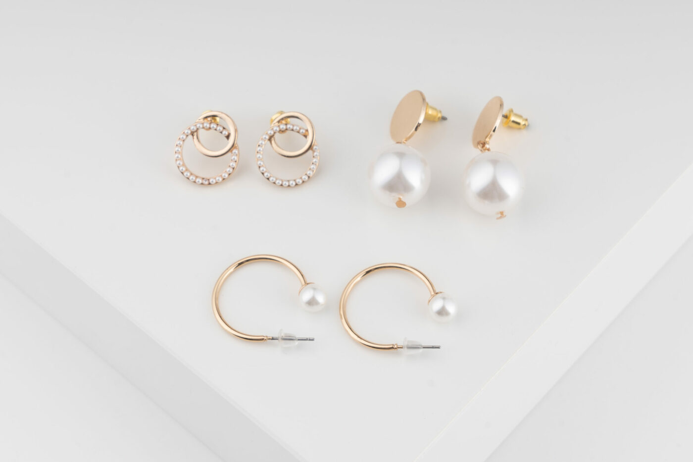 Ein Set von Trisa Accessoires an zierlichen Ohrringen und goldigem Modeschmuck mit weissen Perlen vor weissem Hintergrund.