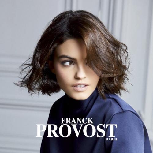Eine junge Frau mit gewellten Haaren, pflegt ihr Haar mit Produkten von Franck Provost.