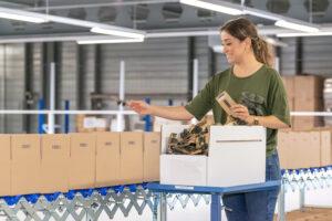 Eine Mitarbeitende der Verkaufslogistik von Trisa Accessoires am Kommissionieren einer Filial-Bestellung.