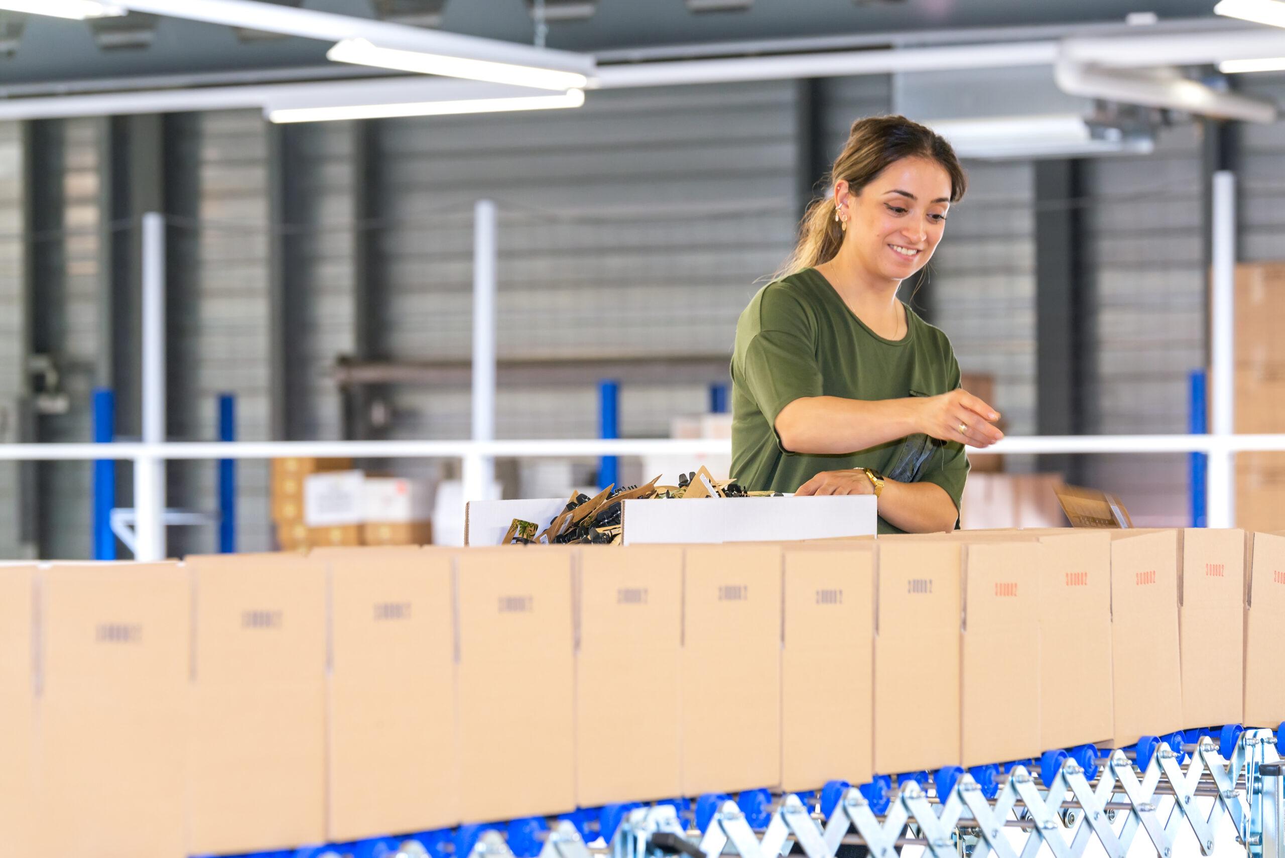 Eine Mitarbeitende der Verkaufslogistik von Trisa Accessoires ist am Kommissionieren einer Kunden-Bestellung.