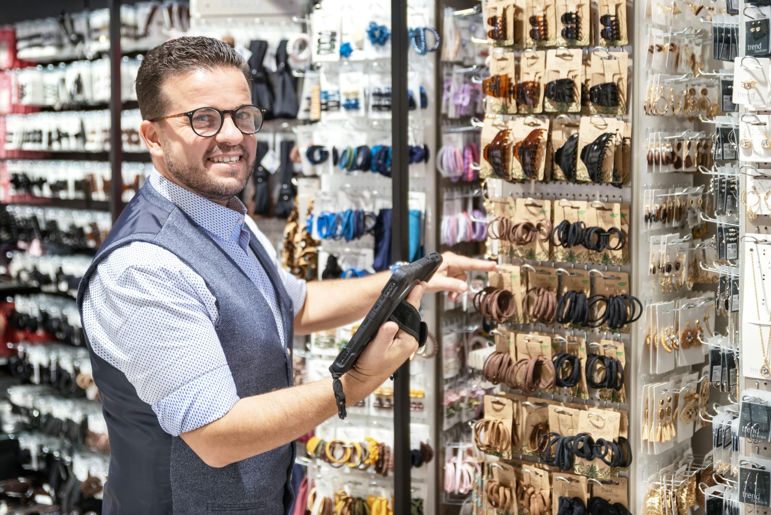Ein POS Services Mitarbeiter von Trisa Accessoires, steht lächelnd am Verkaufsregal und nimmt eine Kundenbestellung auf.