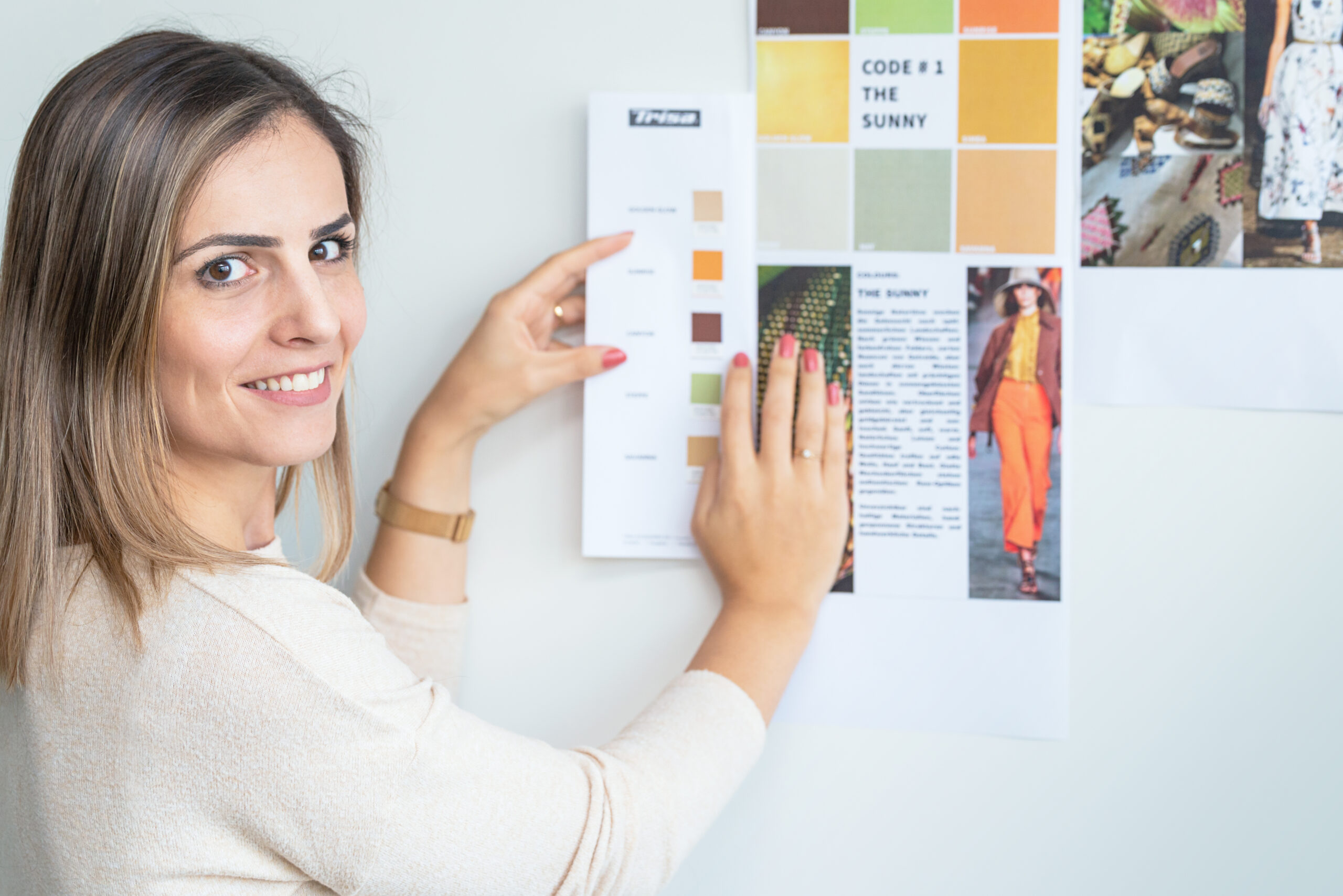 Junge Frau bei der Sortimentsgestaltung einer Haarschmuck Linie von Trisa Accessoires, vor weisser Wand