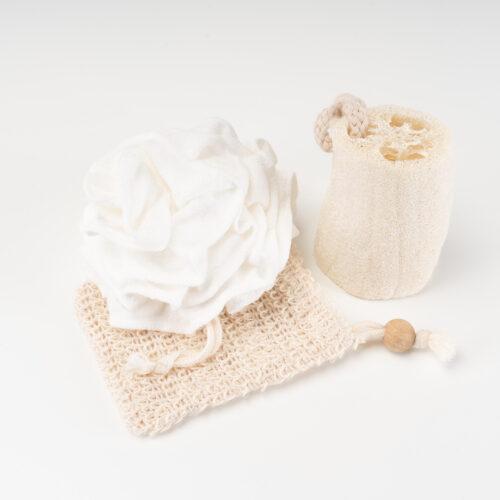 Ein Set an Wellness Artikeln von Trisa Accessoires, aus natürlichen Materialien, bestehend aus Luffa Schwamm, Seifenbeutel und textiler Duschrose, vor weissem Hintergrund.