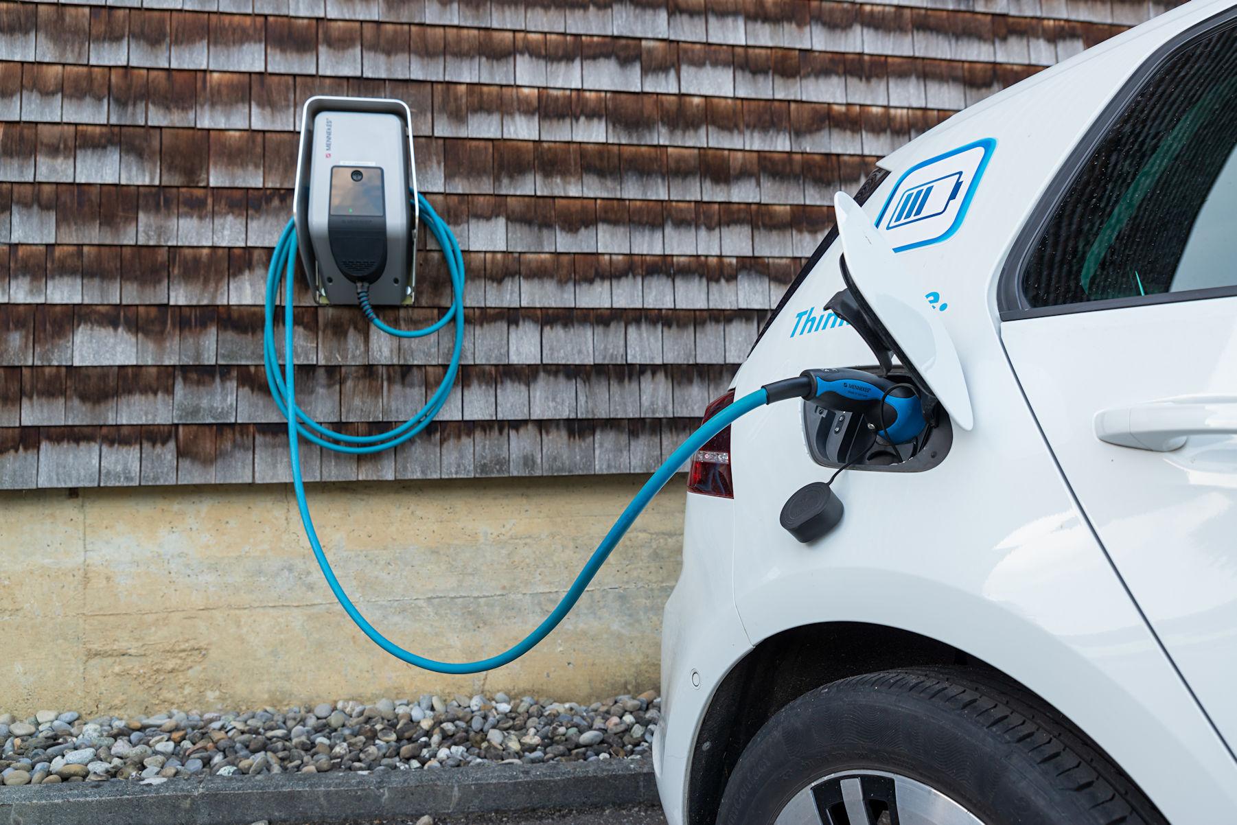 Elektro-Auto an Ladestation bei Trisa Accessoires, aus der Flotte der Betriebsfahrzeuge für den Aussendienst, vor Holzfassade