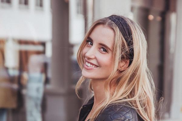 Strahlende junge blonde Frau, arbeitet bei Trisa Accessoires, trägt ein schwarzes Haarband von Trisa Accessoires.