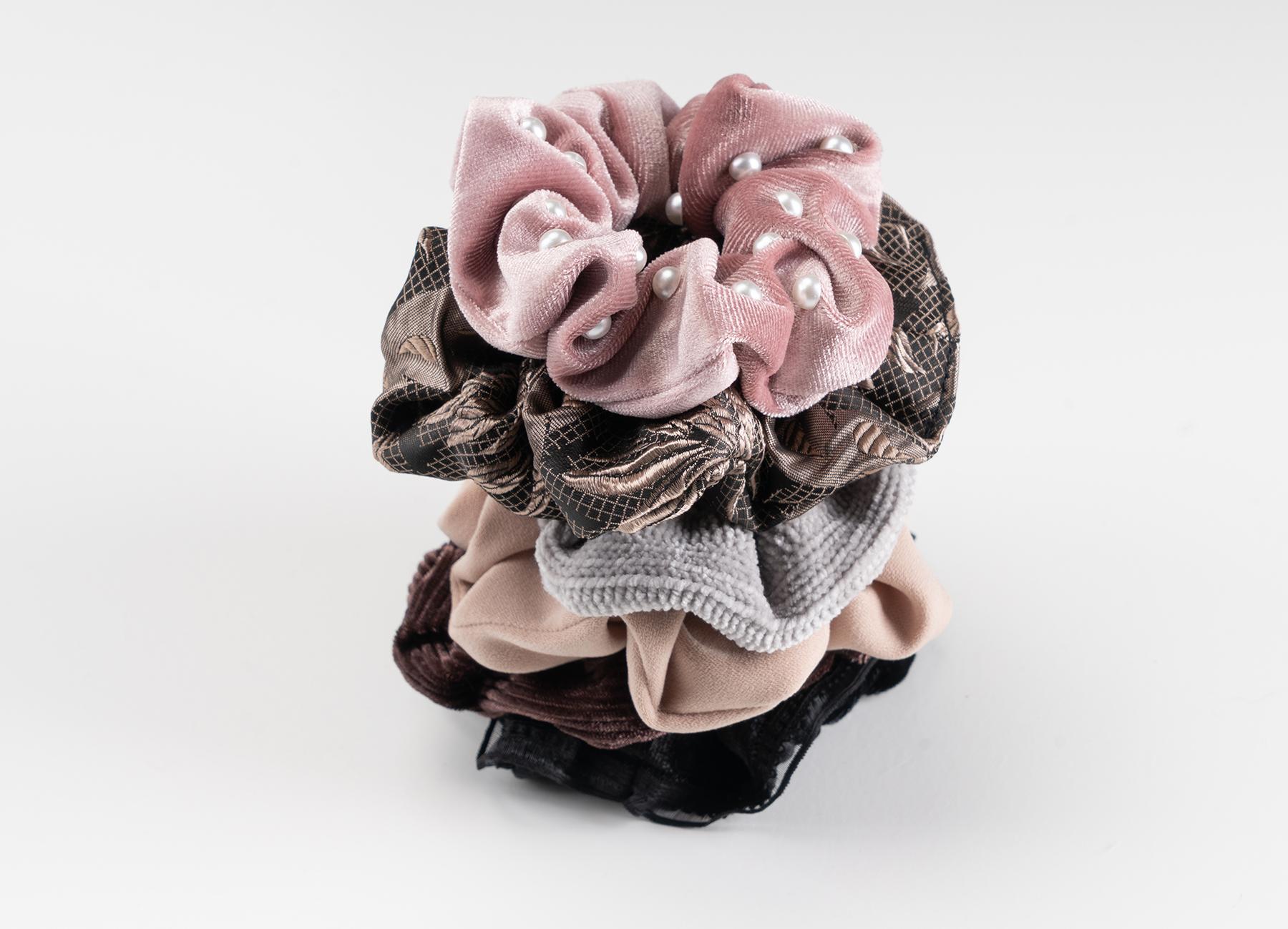 Ein dekoratives Set an Haarschmuck Scrunchies von Trisa Accessoires, in den Farben schwarz, grau, rosa und braun, platziert auf weissem Hintergrund.