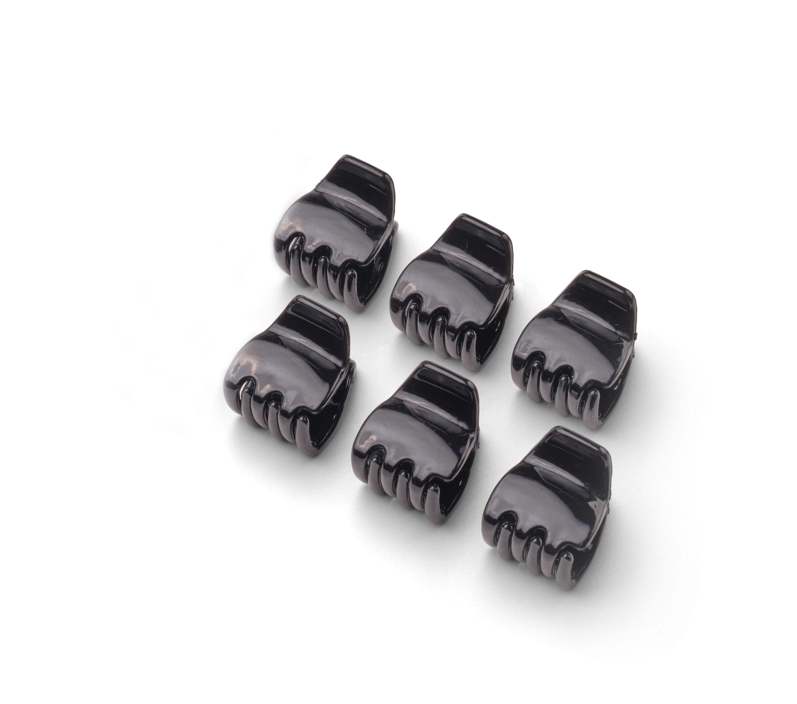 Set aus sechs schwarzen Haarklammern von Trisa Accessoires, ergonomisch geformt, aus flexiblem und strapazierfähigem Material gefertigt, made in Italy, auf weissem Hintergrund.